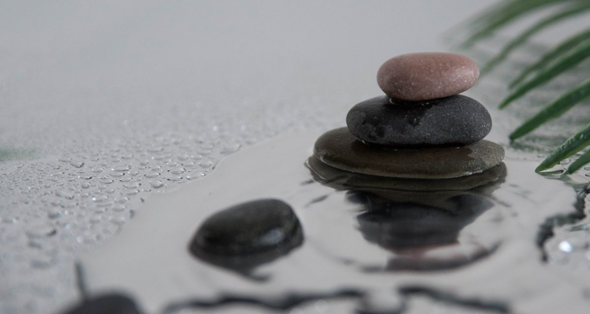 Image of rocks stacked on glass with water on it for post on New Years Resolutions