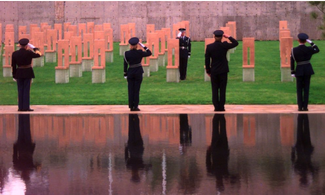 Photo of officers saluting before the empty chairs at the Oklahoma City National Memorial