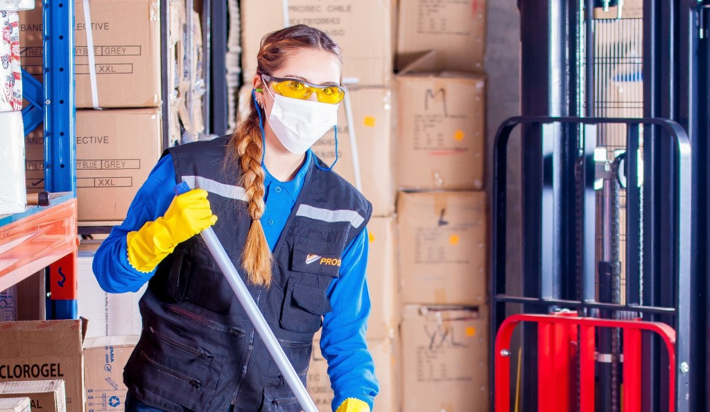Woman wearing mask disinfecting work area from coronavirus