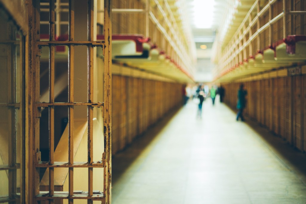 Photo of walkway between rows of prison cells - criminal justice post