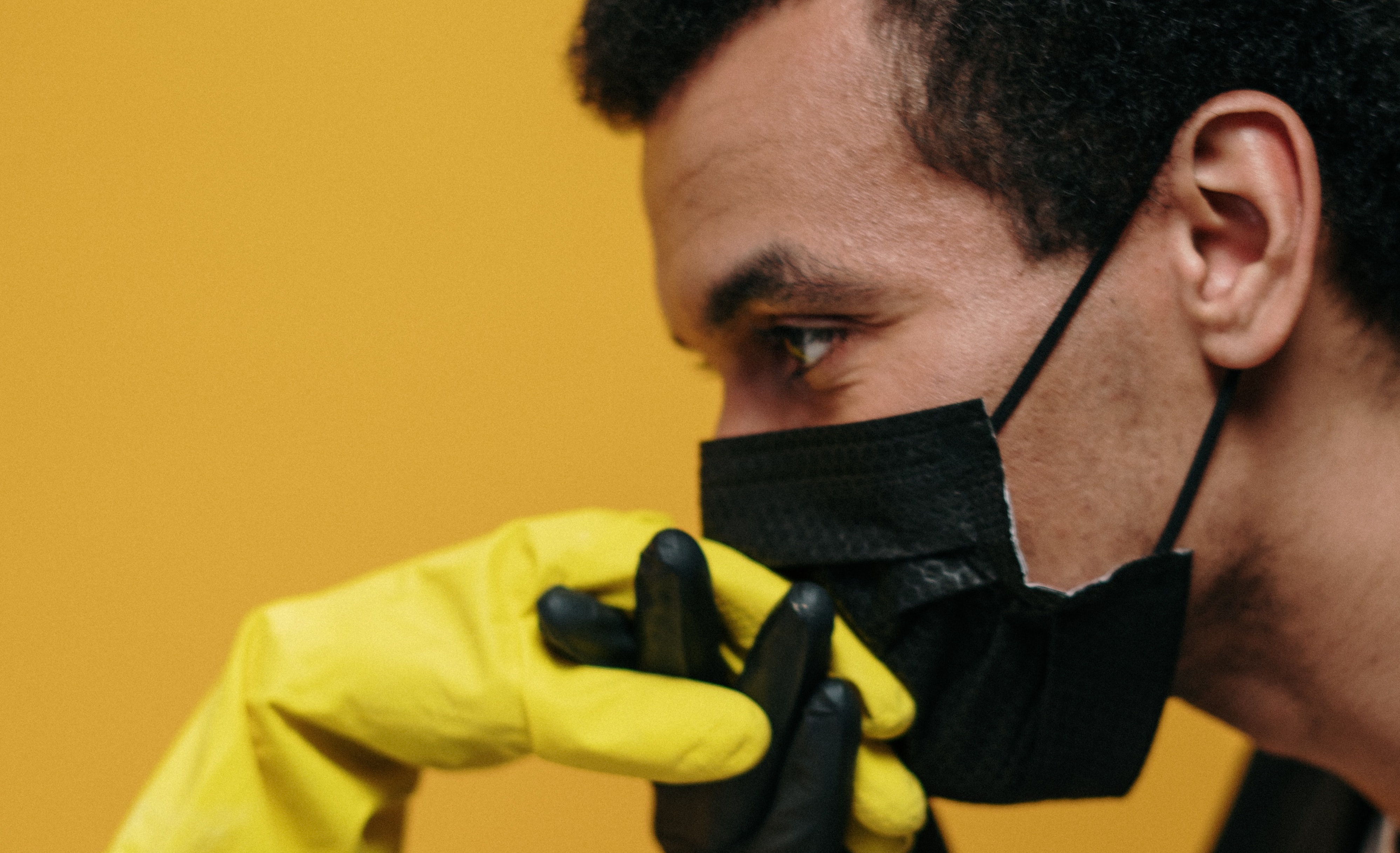 Man in mask kisses hand in yellow rubber glove