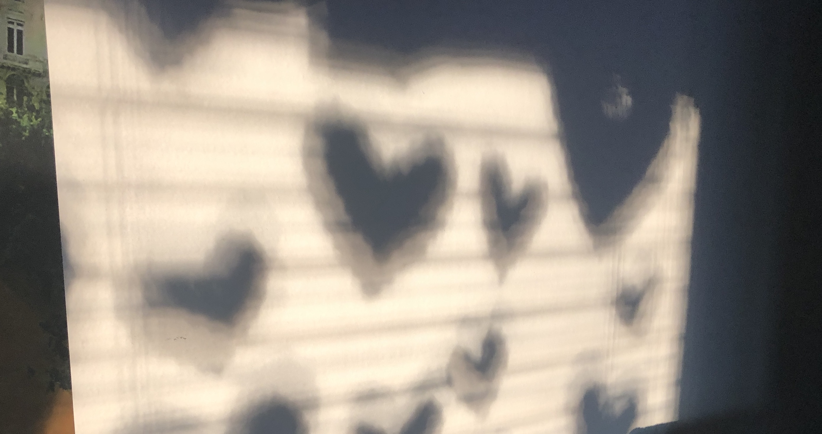 Image of shadows of Covid pandemic cut-out hearts on a wall