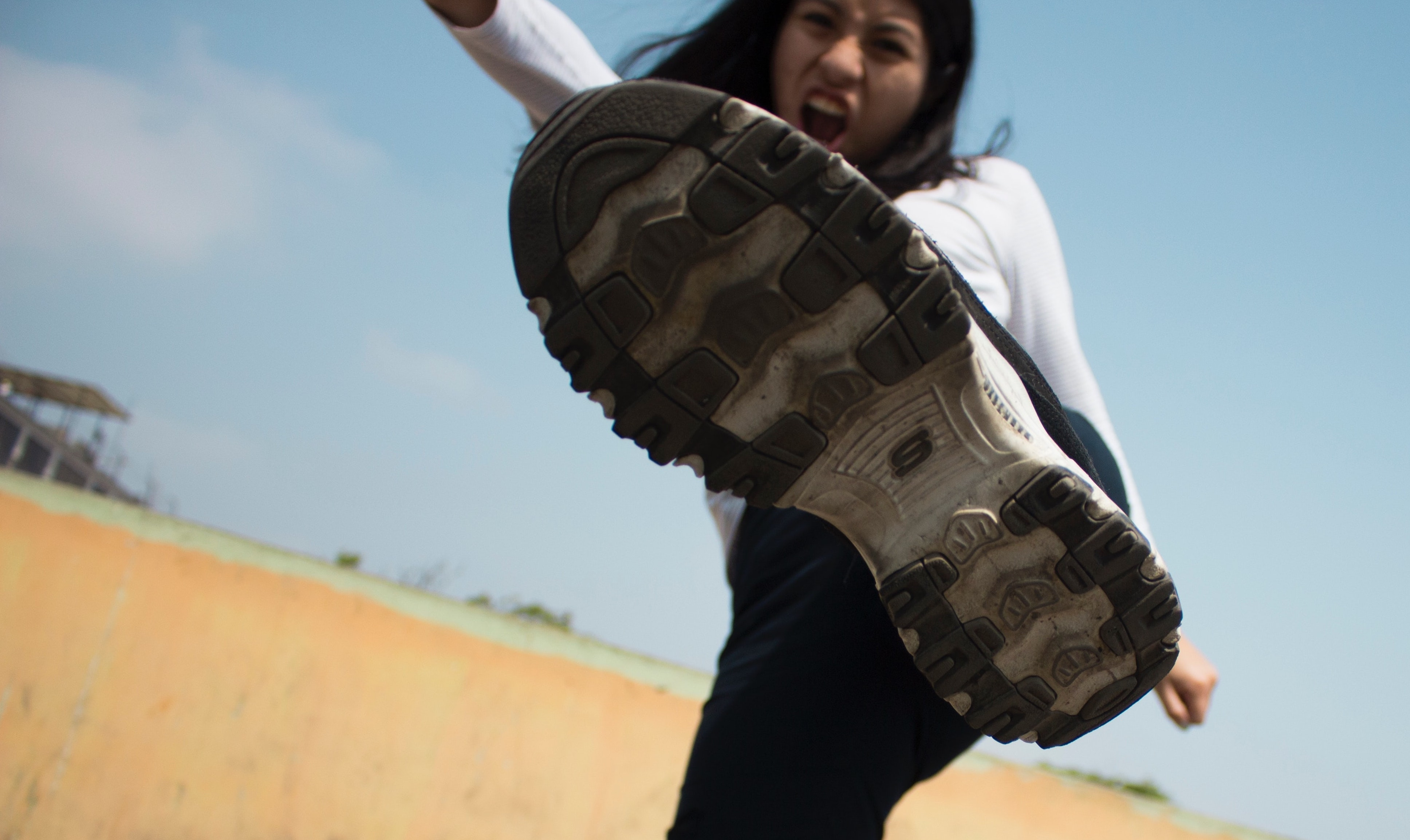 Image of a young woman kicking toward the foreground in climate anger.