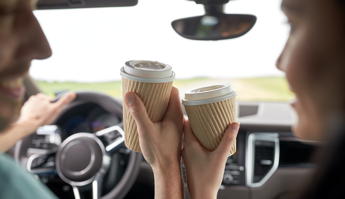 Image of man and woman bumping coffee cups