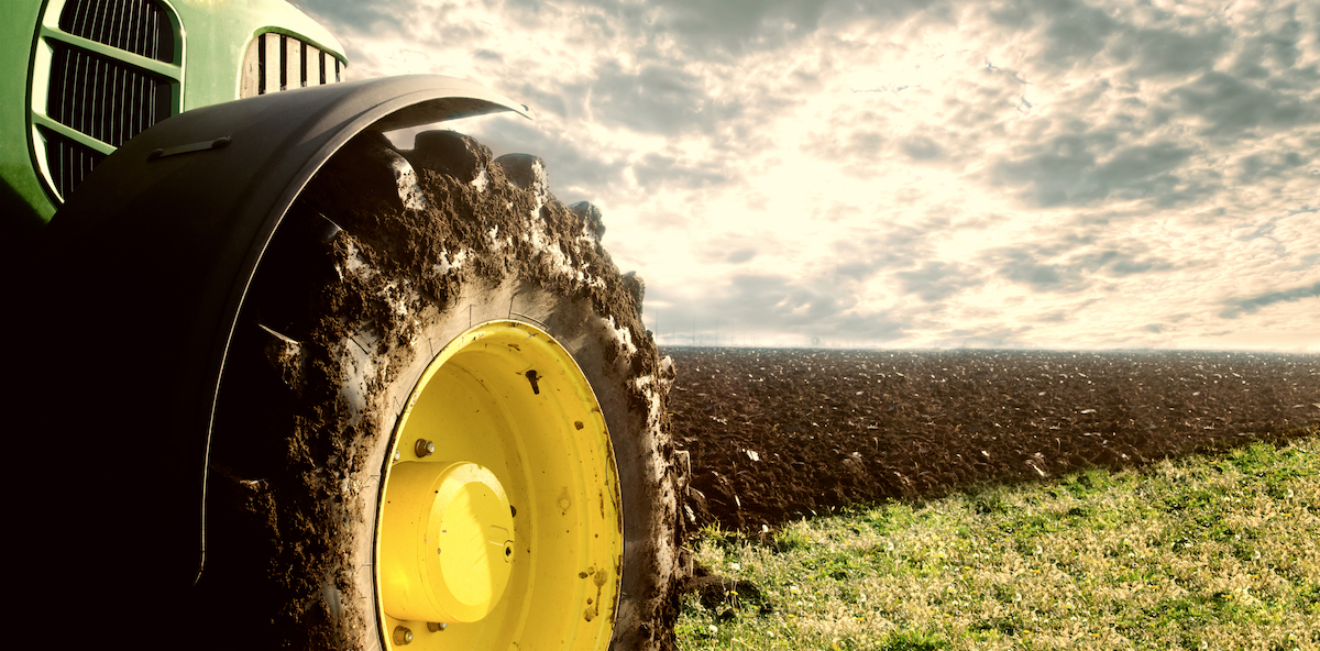 Photo of a tractor with a wheel covered in mud