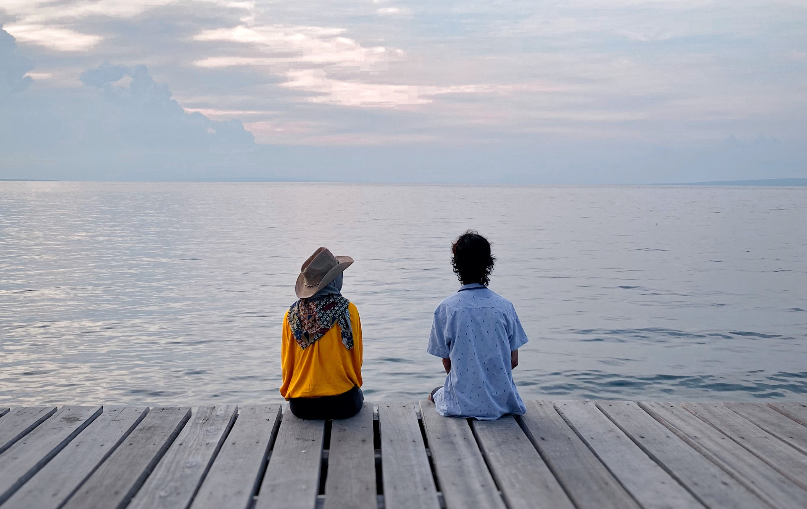 Image of two people sitting on a dock next to a lake
